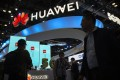Attendees walk past the booth of Huawei Technologies at the PT Expo China trade show in Beijing on October 31. Photo: AP