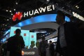 Attendees walk past a display for 5G services from Chinese technology firm Huawei at the PT Expo in Beijing, Thursday, Oct. 31, 2019. Photo: AP