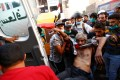 Demonstrators carry a wounded man during the ongoing anti-government protests in Baghdad. Photo: Reuters
