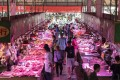 Customers walk past pork stalls at the Dancun Market in Nanning, Guangxi province. Photo: Bloomberg