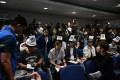 """Six journalists wear protective press helmets with Chinese characters that, when put together, read """"investigate police brutality. Stop police lies"""", during a press conference at the Hong Kong police headquarters on November 4. Photo: AFP"""