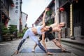Yoga is taking off in China and local and international yogis are setting up schools there. Sara Pei and David Baimbridge demonstrate the triangle pose. Photo: Lin Zhi Yong