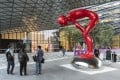 Employees stand next to a sculpture at the Ant Financial headquarters in Hangzhou, China. Photo: Bloomberg