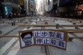 """A protest placard bearing a photo of Hong Kong Chief Executive Carrie Lam is displayed on a blockaded street in Central on November 13. The Chinese characters read: """"Stop manufacturing chaos, stop killing"""". Photo: EPA-EFE"""