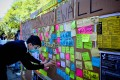 A supporter of Hong Kong's anti-government protests posts a note on a makeshift 'Lennon Wall' at the University of Queensland in Brisbane. Photo: AFP