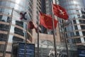 Flags are raised outside the Exchange Square building in Central. Retail investors expect Hong Kong stock exchange's benchmark index to rise next year. Photo: AP