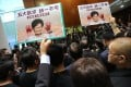 "Pan-democrat lawmakers hold up protest placards saying ""five demands, not one less"", as Chief Executive Carrie Lam arrives at the Legislative Council to deliver her policy address on October 16. Her speech was disrupted to the extent that it had to be delivered by video, a first for Hong Kong. Photo: May Tse"