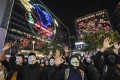 Christmas illuminations form the backdrop as anti-government protesters wearing Guy Fawkes masks hold up their open palms to signify their five demands, at a rally against an emergency mask ban in East Tsim Sha Tsui on November 5. Photo: Felix Wong
