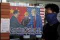 A pro-democracy university student walks past a poster featuring Chinese President Xi Jinping and US President Donald Trump at the campus of the University of Hong Kong on November 6. Photo: AP