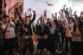 Supporters of pro-democracy candidates celebrate with champagne in Tuen Mun on November 25, as results of the previous day's Hong Kong district council elections come in. Photo: AFP