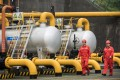 China needs to involve state-owned and private companies in policy making to better address major global problems like climate change. Here, workers walk past pipework and storage tanks at a project operated by Sinopec Chongqing Fuling Shale Gas Exploration and Development a unit of China Petrochemical Corp. Photo: Bloomberg