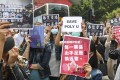"""Protesters at a lunchtime rally in Kowloon Bay on November 26, holding signs saying """"Save PolyU"""", """"Don't forget the bloody price behind every vote"""" and """"True victory is when all five demands are met"""". Photo: Nora Tam"""