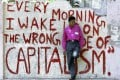 A college student leans against a wall painted with anti-capitalism graffiti in Mumbai, India, in 2004. Photo: AFP