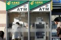 Customers at the China Postal Savings Bank's ATMs in Beijing on 3 February 2007. Photo: AFP