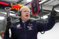Britain's Prime Minister Boris Johnson prepares to change a wheel on a Formula One car during his visit to Red Bull Racing in Milton Keynes, Britain, on Wednesday. Photo: Reuters