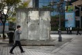 A man walks past a section of the Berlin Wall displayed at 'Berlin Plaza' in central Seoul. Photo: AFP