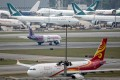 A Hong Kong Express Airways Ltd. aircraft taxis past a Hong Kong Airlines Ltd. aircraft, foreground, and a Cathay Pacific Airways Ltd. cargo aircraft at Hong Kong International Airport in Hong Kong, China, on Tuesday, March 5, 2019. Cathay is in talks to buy shares in Hong Kong's only budget airline Hong Kong Express from Chinese conglomerate HNA Group Co., as Asia's biggest international carrier seeks to gain a foothold in the region's booming low-cost travel market. Photo: Bloomberg