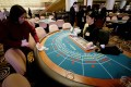 A cleaner wipes down a gambling table just before the opening of the new Sands Casino in Macau on 18 May 2004. Sands is the first American operator of gambling facilities in the Chinese Special Administrative Region (SAR). Photo: AFP