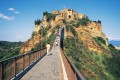Tourists walk up the single metal footbridge from the main road below to the village of Civita di Bagnoregio in the Latium region near Rome, Italy. The village is perched on a plateau of volcanic rock surrounded by steep ravines and is home to just a dozen residents. Photo: DeAgostini/Getty Images