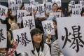 """Medical professionals hold up signs protesting about the health care system reaching """"bursting point"""" at Queen Elizabeth Hospital in Jordan, Hong Kong, on January 26. Photo: Felix Wong"""