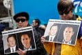 People hold placards calling for China to release Michael Spavor and Michael Kovrig outside a court hearing for Huawei executive Meng Wanzhou in Vancouver in March. Photo: Reuters