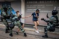 Police chase down a couple wearing facemasks in Central in October after the introduction of a mask ban. Photo: AFP