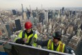Work continues on an outdoor observation deck on an office building in New York. In the US, fears of a recession have fallen dramatically since the summer. Photo: AP