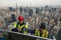 Workers on an outdoor observation deck on the 30 Hudson Yards office building in New York on March 8, 2019. Economists expect US economic growth to slow this year and next, but they say the economy will avoid a recession. Photo: AP