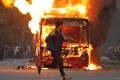 A man runs past a burning bus set on fire by demonstrators against India's new religion-based citizenship law. Photo: Reuters