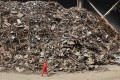 """A worker walks past piles of scrap steel at a plant of Dongbei Special Steel Group in Dalian, Liaoning province, in March 2018. The company failed to repay 10 batches of corporate bonds worth US$1 billion from March 2016 onwards, leading to a legal battle between the company and its 1,911 creditors. After a court-ordered """"bankruptcy restructuring"""" plan in which creditors lost 78 per cent of their money, and a windfall from a steel price rally, the company bounced back. Photo: Reuters"""