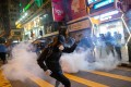 Protesters react after riot police fire tear gas in Tsim Sha Tsui on Christmas Eve. Photo: EPA-EFE