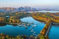 Donghu Lake in Wuhan, the capital of central China's Hubei province, is flanked by high-rise buildings in July. China is undergoing rapid urbanisation, with nearly 60 per cent of the population living in cities. Photo: Xinhua