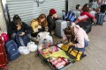 Mainland tourists with suitcases full of shopping sit on the pavement in Sheung Shui. Photo: Dickson Lee