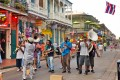 """Bourbon Street in the French Quarter of New Orleans, and a """"second line"""" jazz band parades seeking donations from tourists and locals. Photo: Shutterstock"""