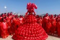 Kong Ning, a 62-year-old artist from Inner Mongolia, China, creates dresses that highlight pressing issues – such as this dress made of red masks she designed to raise awareness of global warming. The red masks represent people feeling hot and burned.