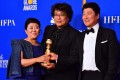 South Korean film director Bong Joon-ho (centre) poses with the best foreign language Golden Globe for Parasite. The win adds to the Oscar buzz surrounding the film. Photo: AFP