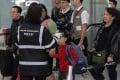 A health surveillance officer checks the temperature of passengers at Hong Kong International Airport. Photo: AP