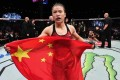 Zhang Weili celebrates with the Chinese flag after winning the strawweight title. Photo: Brandon Magnus/Zuffa LLC
