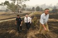 Australian Prime Minister Scott Morrison (centre) tours a farm that was ravaged by fire in Sarsfield, Victoria, on January 3. Photo: AP