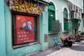 A man sits in an alley next to a screen with the image of China's President Xi Jinping in Macau on December 19, 2019 as the city marks the 20th anniversary of the handover from Portugal to China. Photo: AFP