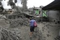 A resident checks his damaged house at Laurel, Batangas province on Tuesday. Photo: AP