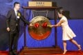 Jiumaojiu chairman Guan Yihong (left) and his wife Yang Sanyin strike the ceremonial gong to mark the company's trading debut on the Hong Kong stock exchange on Wednesday. Photo: Jonathan Wong