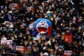 A protester in a Doraemon costume joins a march on New Year's Day, with demonstrators holding up their hands to call for better governance and democratic reforms in Hong Kong. Photo: Reuters