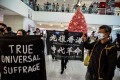 Protesters march through Harbour City shopping mall in the Tsim Sha Tsui on December 21, 2019. Photo: AFP