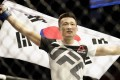 Jung Chan-sung celebrates with his native flag after defeating Dennis Bermudez in 2017. Photo: AFP
