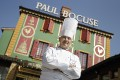 Chef Paul Bocuse poses outside his famed restaurant Auberge du Pont de Collonges in France in March 2011. Photo: AP