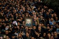 Protesters hold up an image of slain Iranian general Qassem Soleimani during a demonstration in Tehran. Photo: Bloomberg