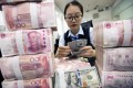 A clerk counts banknotes at a bank outlet in Hai'an, Jiangsu province. Photo: EPA-EFE