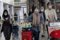 Travellers wear masks in the arrival hall of Hong Kong International Airport on Wednesday as China confirmed 440 cases of Wuhan pneumonia with nine deaths. Photo: EPA