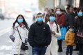 Chinese residents wear masks while waiting at a bus station near the closed Huanan Seafood Wholesale Market, which has been linked to cases of a new strain of Coronavirus. Photo: EPA-EFE